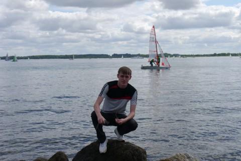 Я на камне на фоне одинокого белеющего парусника в Ostsee